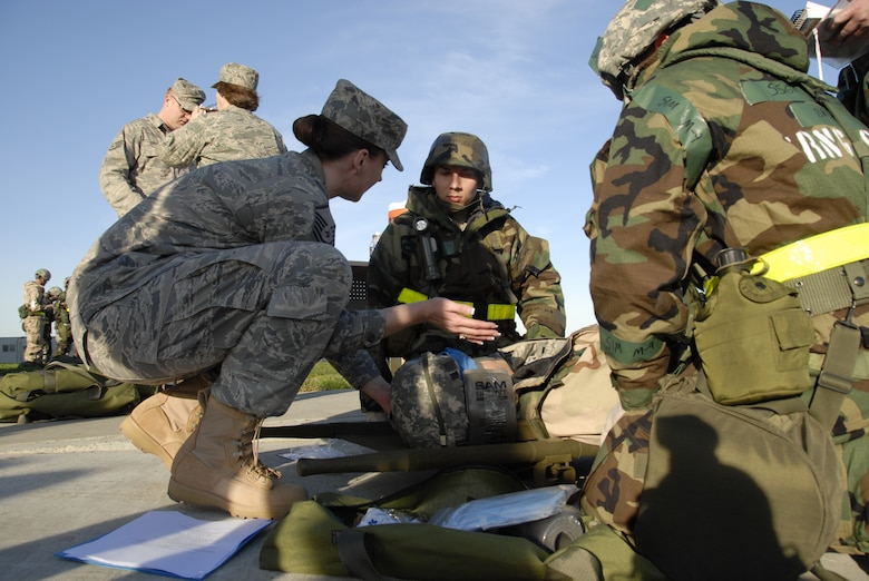 Master Sgt. Summer Mize, a senior health technician from the 129th Medical Group, demonstrates proper head restraint technique to Staff Sgt. Byron Estrada, a client systems technician from the 129th Communications Flight, during war skills training at Moffett Federal Airfield, Calif., Feb. 5, 2011. The 129th Rescue Wing is preparing for an upcoming Operation Readiness Inspection in December 2011.  (Air National Guard photo by Tech. Sgt. Ray Aquino/RELEASED)