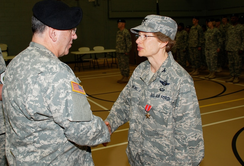 U.S. Air Force Colonel Carol Timmons, Delaware National Guard, is congratulated by Maj. Gen. Francis Vavala, Adjutant General, Delaware National Guard, on Feb. 5, 2011 after she was awarded a Bronze Star Medal in Wilmington, Del. Col. Timmons received the award for her meritorious achievement while the deputy commander, 455th Expeditionary Operations Group, 455th Air Expeditionary Wing, Bagram Air Base, Afghanistan, May 3 to Sept. 3, 2008 in support of Operation Enduring Freedom. (U.S. Army photo/Lt. Col. Leonard Gratteri, Delaware National Guard)