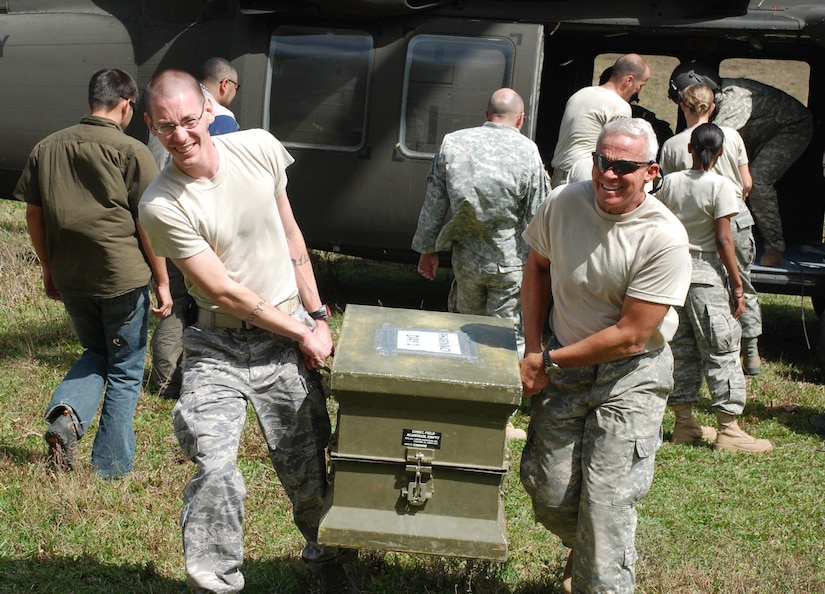 SOTO CANO AIR BASE, Honduras - 1Lt. Jonathan Snyder (left), physician assistant with Joint Task Force-Bravo's Medical Element, and MEDEL commander Col. (Dr.) Michael Hoilien, carry medical supplies, delivered by the 1-228th Aviation Regiment, during a medical readiness training exercise in Montana de la Flor Jan. 28.  The exercise was a coordinated effort between JTF-B, the Honduran Ministry of Health, the Honduran Army, Honduran Mission LeMars and volunteers from the University of South Dakota to to provide basic medical services to the people there. (U.S. Air Force photo/Capt. John T. Stamm)