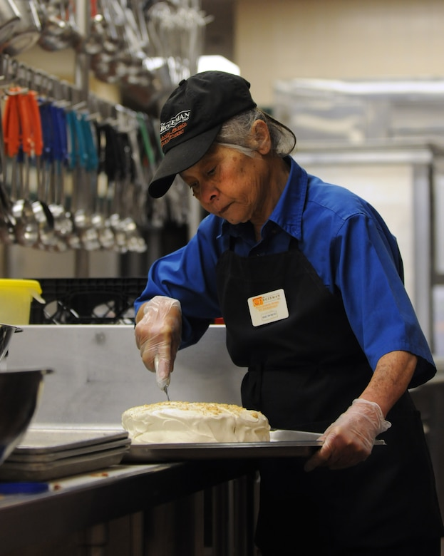 Bernie Tubbs, 90th FSS, cuts cake for lunch dessert at Chadwell Dining Facility on F. E. Warren Air Force Base, Wyo. Jan. 28. (U.S. Air Force photo by R.J. Oriez)