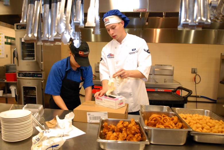 Airman Joshua Herrington, 90th FSS, reaches for gloves prior to handling chicken fingers, onion rings and potato nuggets prepared for the snack line at the Chadwell Dining Facility on F. E. Warren Air Force Base, Wyo. on Jan. 28. (U.S. Air Force photo by R.J. Oriez)
