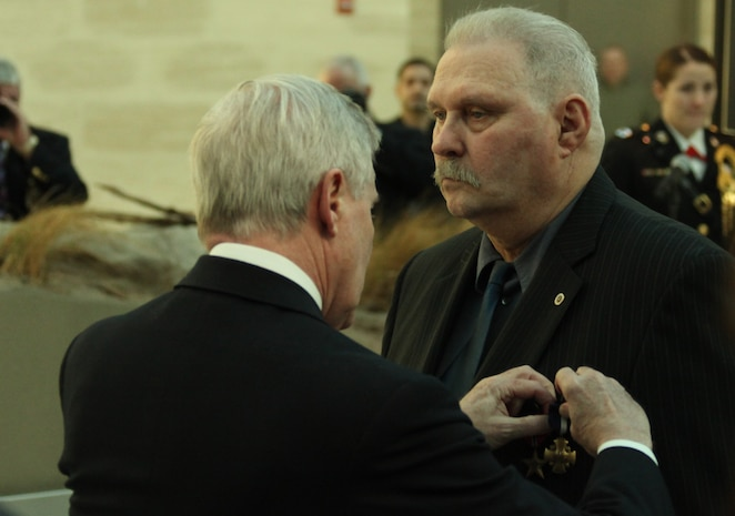 Secretary of the Navy Ray Mabus presents the Navy Cross to Ned Seath Feb. 11, 2011. Seath also recieved a Bronze Star with a V for valor from actions the night before he commited the acts that earned him the Navy Cross.