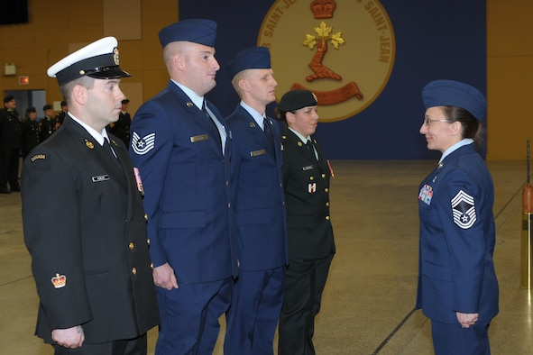 """U.S. Air Force Tech. Sgts. Clifford Fallico (second from left), Air Forces Northern intelligence, surveillance and reconnaissance planner, and Robert Carnall, 702nd Computer Support Squadron system administrator (third from left), stand before Chief Master Sgt. Angela Abshire (right), director of standards at the Noncommissioned Member Professional Development Center, at the graduation ceremony where they both earned the """"Comradeship Award"""" from the Canadian Intermediate Leadership Program, Canadian Forces College, Noncommissioned Member Professional Development Center, St. Jean Sur Richlieu in Quebec, Canada.  Only four of 120 students received the peer-voted award. (Photo by Mr. Christian Jaques)"""
