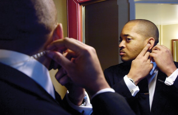 Tech. Sgt. Vanderbill King II, non-commissioned officer in charge of the squadron's mission supporting the Secret Service, attaches his communications ear piece during training at a local hotel. The team will turn a hotel room into a communications center in a matter of minutes. (Air Force photo by Margo Wright)