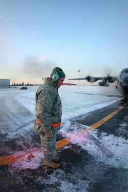 KULIS AIR NATIONAL GUARD BASE, Alaska - Maj. Matthew Friese, a chaplain with the 176th Wing, blesses a C-130 before a flight, Feb. 12, 2011. The C-130 along with 10 other aircraft from the 176th Wing was flown from Kulis to Joint Base Elmendorf-Richardson during a ceremonial flight. The Wing is relocating from Kulis to JBER per the 2005 Defense Base Closure and Realignment proposal.  Alaska Air National Guard photo by Tech. Sgt. Julie Arthur.