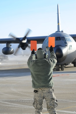JOINT BASE ELMENDORF-RICHARDSON, Alaska - Senior Airman Alexander Van Nice, a crew chief with the 176th Aircraft Maintenance Squadron, marshals in a C-130 from the 144th Airlift Squadron, Feb. 12, 2011. The aircraft was flown from Kulis to Joint Base Elmendorf-Richardson during a ceremonial flight. The 176th Wing is relocating from Kulis to JBER per the 2005 Defense Base Closure and Realignment proposal.  Alaska Air National Guard photo by Master Sgt. Shannon Oleson.