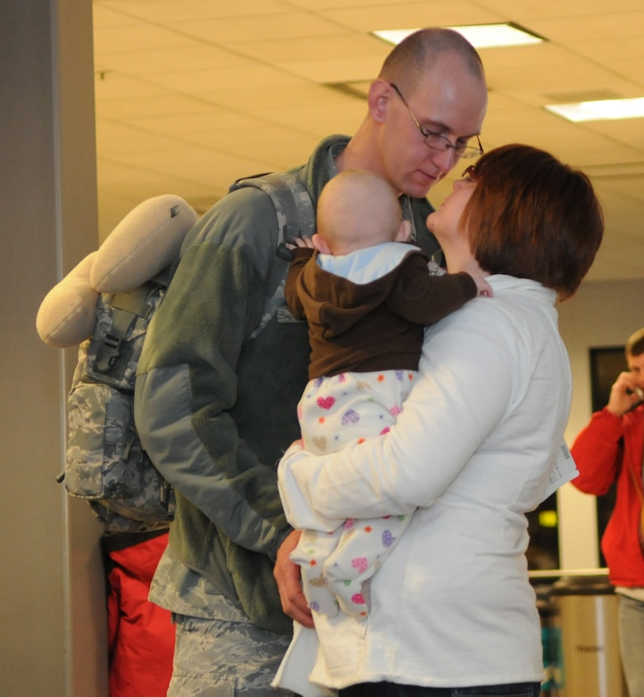Senior Airman Justin Lemon gets a last kiss from his wife and baby before boarding his flight at the Salt Lake City International airport on February 3, 2011. Airman Lemon is one of the 33 members with the Utah Air National Guard's 151st Security Forces Squadron who left for a six-month deployment to Iraq.(U.S. Air Force photo by Master Sgt. Gary J. Rihn)(RELEASED)