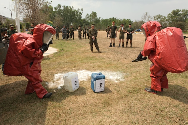 February 14, 2011, U.S. Marines with the Chemical Biological Radiological Nuclear high-yield Explosive (CBRNE) detachment, 31st Marine Expeditionary Unit (MEU), 3rd Marine Expeditionary Brigade (MEB), observe two Royal Thai Navy Sailors conduct a mock chemical contamination drill in Samesan, Kingdom of Thailand, for Exercise Cobra Gold 2011. For three decades, Thailand has hosted Cobra Gold, one of the largest land-based, joint, combined military training exercises in the world.  A successful Cobra Gold 2011 results in increased operational readiness of U.S. and Thai forces and matured military to military relations between the two countries.