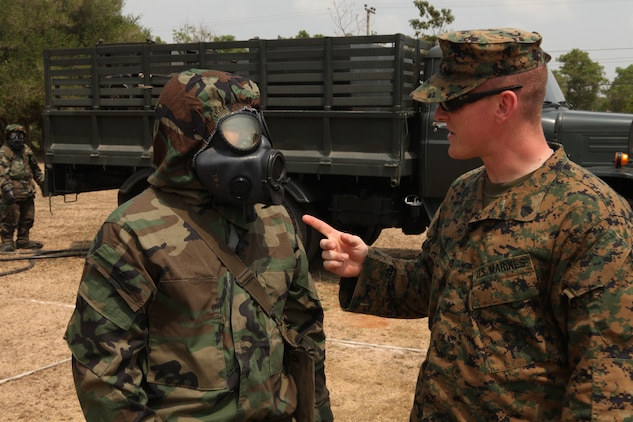 February 14, 2011, Sgt. Bradley Mowery, the Chemical Biological Radial Nuclear high-yield Explosive (CBRNE) detachment chief, with the 31st Marine Expeditionary Unit (MEU), 3rd Marine Expeditionary Brigade (MEB), and a Royal Thai Navy Sailor share techniques during a mock chemical contamination drill in Samesan, Kingdom of Thailand, for Exercise Cobra Gold 2011. For three decades, Thailand has hosted Cobra Gold, one of the largest land-based, joint, combined military training exercises in the world.  A successful Cobra Gold 2011 results in increased operational readiness of U.S. and Thai forces and matured military to military relations between the two countries.