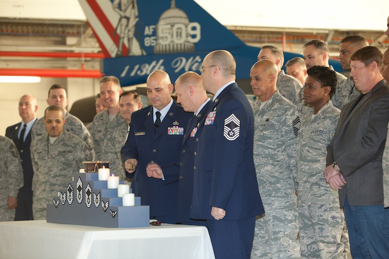 Chief Master Sgt. Louis R. Keeler, Chief Master Sgt. Kevin W. Kling, and Chief Master Sgt. James T. Mathews (left to right) extinguish the candles during their promotion ceremony. The 113th Maintenance Squadron held its first ever pining of three Chief Master Sergeants during a promotion ceremony on February 12, 2011 at Hanger 18, Andrews Air Force Base (U.S Air Force photo by Tech. Sgt. Gareth Buckland/Released)