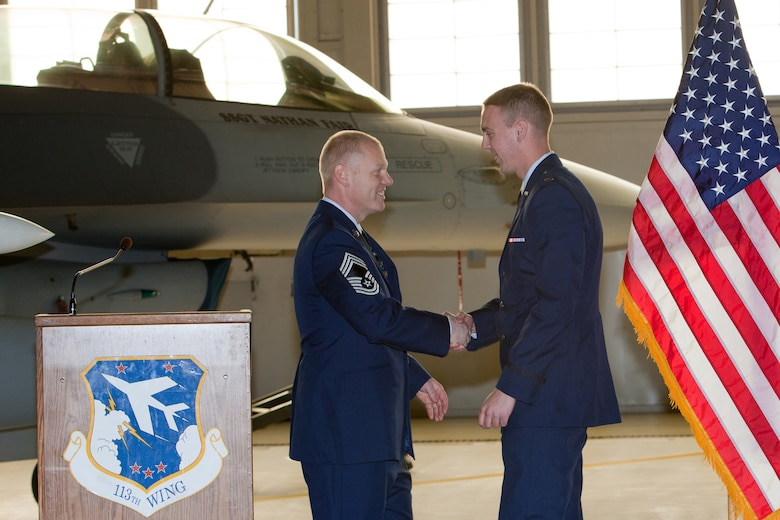 CMSgt Kevin Kling presents his son 2nd Lieutenant Adam Kling with a coin during his promotion ceremony. The 113th Maintenance Squadron held its first ever pining of three Chief Master Sergeants during a promotion ceremony on February 12, 2011 at Hanger 18, Andrews Air Force Base (U.S Air Force photo by Tech. Sgt. Gareth Buckland/Released)