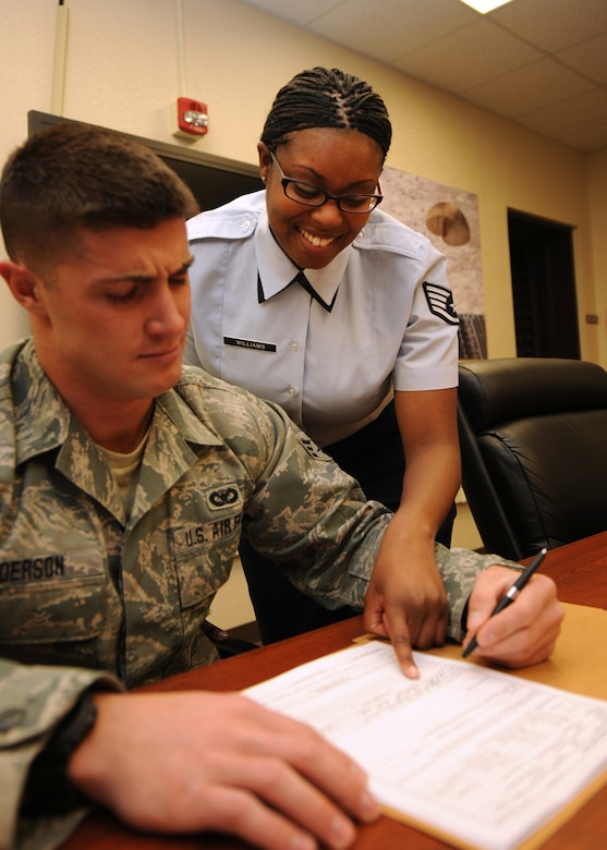 U.S. Air Force Staff Sgt. Takeya A. Williams helps Senior Airman Phil Anderson complete necessary administrative requirements at Hancock Field Air National Guard Base Syracuse, NY on 14 Feb 2011.  Staff Sgt. Williams is a member of the 174th Fighter Wing's Military Personnel Flight and is also an enlisted council member. (U. S. Air Force Photo by Staff Sgt. Ricky Best/RELEASED)