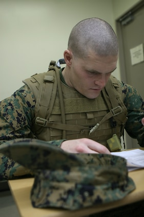 Capt. Aaron Schnetzler, a Marine Aviation Logistics Squadron 12 air speed officer, goes over his test as part of the Humvee Egress Awareness Training course here Feb. 16. The rolling action of a humvee hit by an improvised explosive device was simulated by a machine.