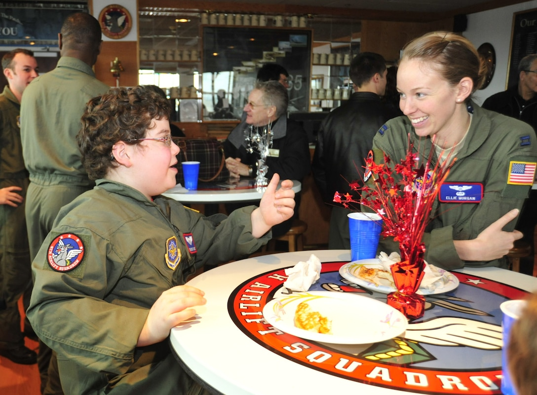 Owain Weinert, left, 9, speaks to Capt. Ellie Morgan, 4th Airlift Squadron pilot, about the television show 'Tom and Jerry' while eating lunch during the Pilot for a Day program Feb. 15 at Joint Base Lewis-McChord, Wash. (U.S. Air Force photo/Airman 1st Class Leah Young)