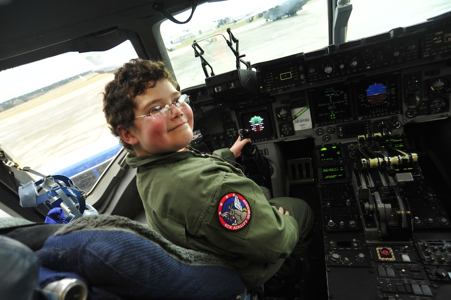 Nine-year-old Owain Weinert smiles as he sits in the pilot seat of a C-17 Globemaster III as part of the Pilot for a Day program Feb. 15 at Joint Base Lewis-McChord, Wash. Pilot for a Day is an Air Force program that enables challenged youth a chance to visit an Air Force squadron, becoming part of the team in the process. (U.S. Air Force photo/Airman 1st Class Leah Young)