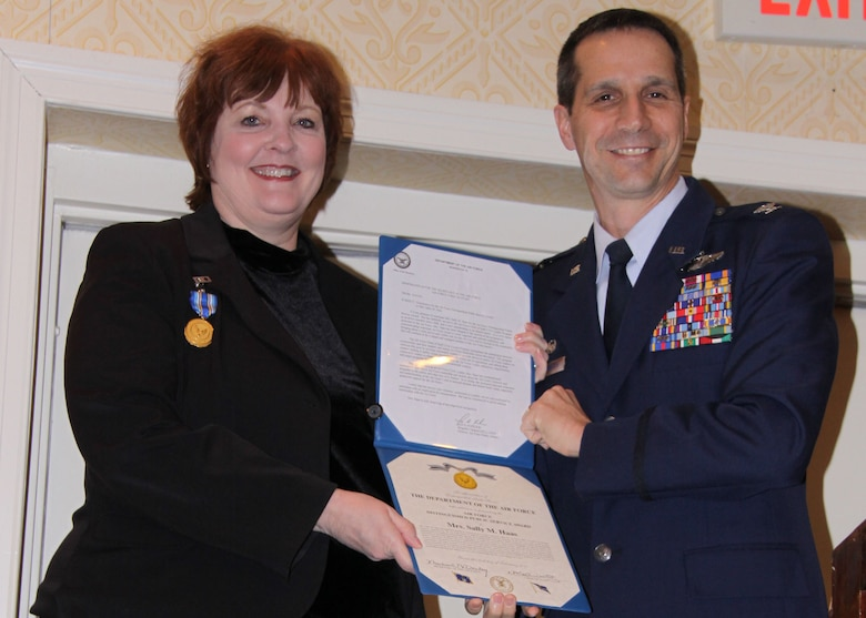 Mrs. Sally Haas, Pittsburgh Airport Area Chamber of Commerce president, is honored by Col. Jeffrey T. Pennington, 911th Airlift Wing commander, during a breakfast briefing Feb. 11, for an award she recently received from the Secretary of the Air Force.   Secretary of the Air Force, Michael B. Donley, presented Mrs. Haas with the Air Force Distinguished Public Service Award during a ceremony Feb. 4 at Joint Base Anacostia-Bolling in Washington, D.C.  It is the highest honorary civilian award the Secretary of the Air Force may grant to a private citizen.  Mrs. Haas earned the award for her advocacy of Air Force issues and for her dedicated support of Airmen and their families while serving as a member of the Air Force Chief of Staff Civic Leader Program.(U.S. Air Force photo/By Senior Master Sgt. Mark Winklosky)