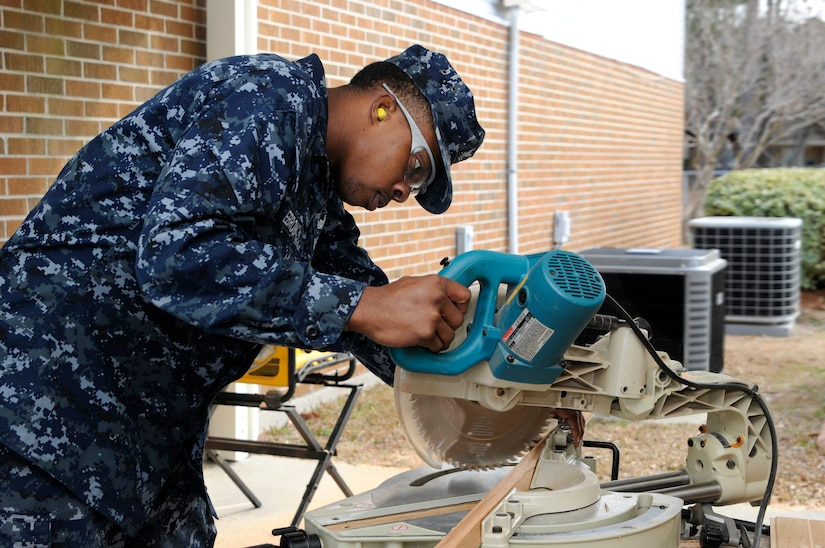 Ship's Serviceman 2nd Class James Ebron, attached to the Naval Support Activity on Joint Base Charleston - Weapons Station, lines up a chop saw to cut a piece of molding trim that will be used during a refurbishment project of the Unaccompanied Personal Housing offices on JB CHS - WS,  Feb. 16. (U.S. Navy photo/Machinist's Mate 3rd Class Brannon Deugan)