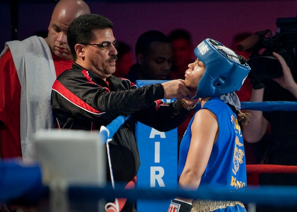 All Marine Boxing Team head coach Jesse Ravelo secures Lance Cpl. Melissa O. Parker's headgear before her bout at the 2011 Armed Forces Championships, Lackland Air Force Base, Texas, Feb. 18.