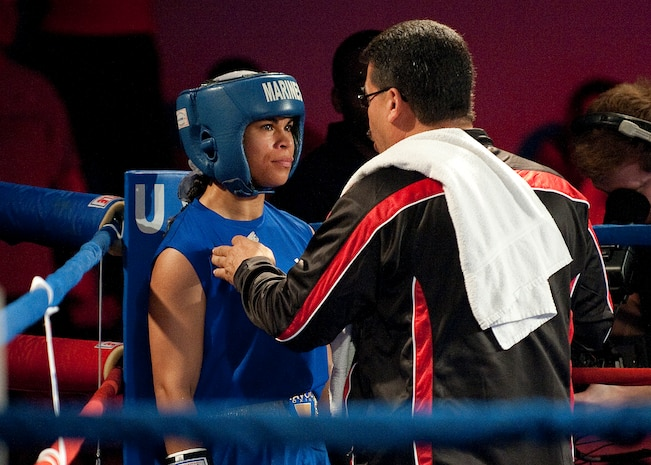 Lance Cpl. Melissa O. Parker listens intently as All Marine Boxing Team head coach Jesse Ravelo gives her pointers in between rounds during her Feb. 18 bout against Army Reserve Spc. Caroline R. Barry