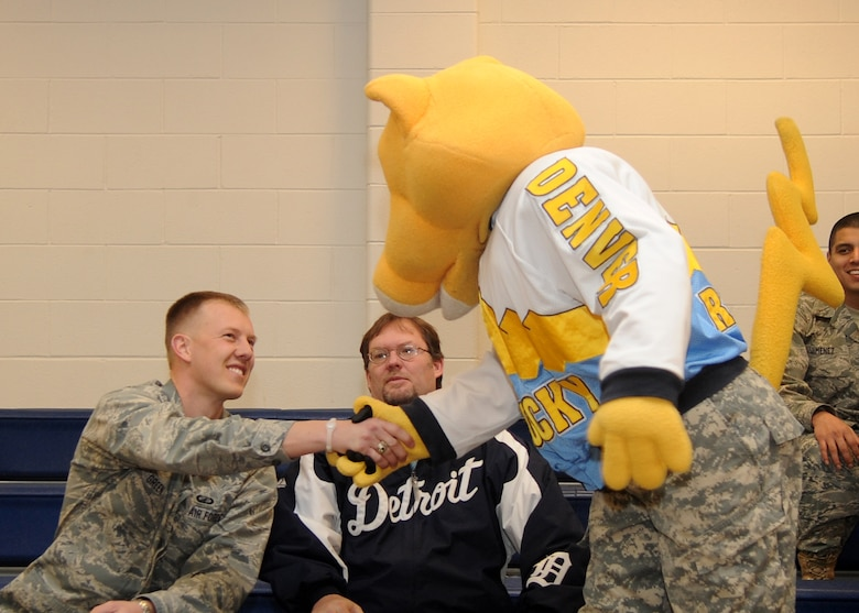Buckley Air Force Base, Colo.-  1st Lt. Kenny Green, 460th Comptroller Squadron, shakes hands with the Denver Nuggets mascot, Rocky February 17, 2011. The local radio station, 98.5 KYGO came to Buckley AFB to celebrate military appreciation day. ( U.S. Air Force Photo by Airman 1st Class Marcy Glass )
