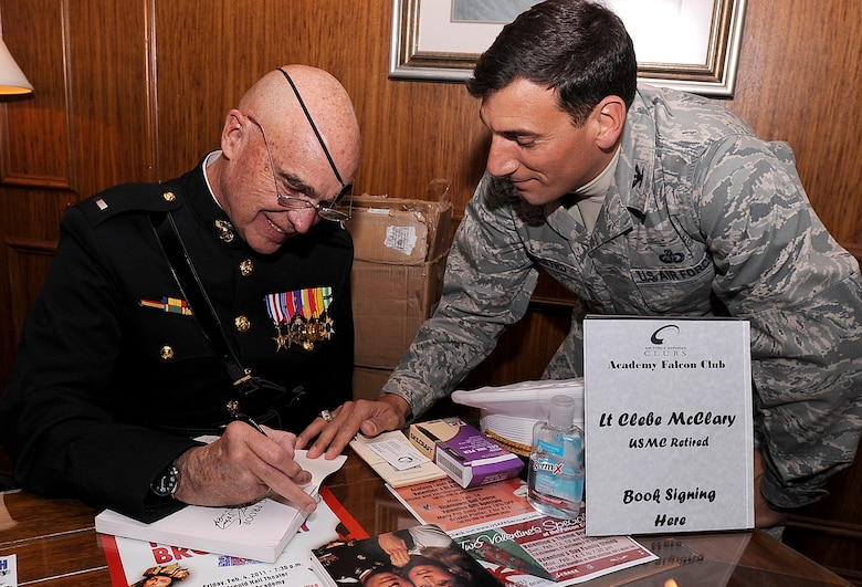 """Retired Marine 1st Lt. Clebe McClary signs a copy of """"Living Proof"""" for Col. Rick LoCastro in the Falcon Club after the Air Force Academy's National Prayer Luncheon Feb. 10, 2011. Lieutenant McClary was injured while serving in Vietnam. Colonel LoCastro is the 10th Air Base Wing commander. (U.S. Air Force photo/Mike Kaplan)"""