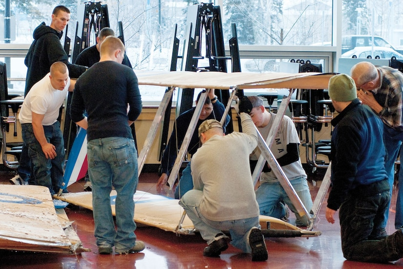 Volunters from Joint Base Elmendorf-Richardson put together an ultra-light model plane at Begich Middle School for the Build-a-Plane program, Feb. 12. The plane was donated by the 3rd Maintenance Squadron. (U.S. Air Force photo/Airman 1st Class Jack Sanders)