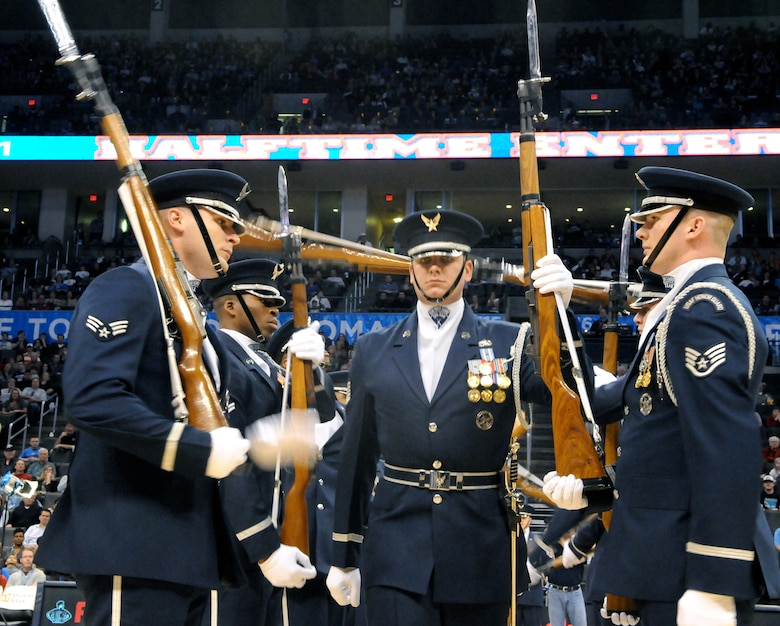 Tech. Sgt. Michael Doss, member of The U.S. Air Force Honor Guard drill team, walks through the line of twirling M-1 rifles during a performance Feb. 15 at the Oklahoma City Thunder's military appreciation night. The performance is Sergeant Doss' final performance with drill team. (U.S. Air Force photo by Airman 1st Class Tabitha N. Haynes)