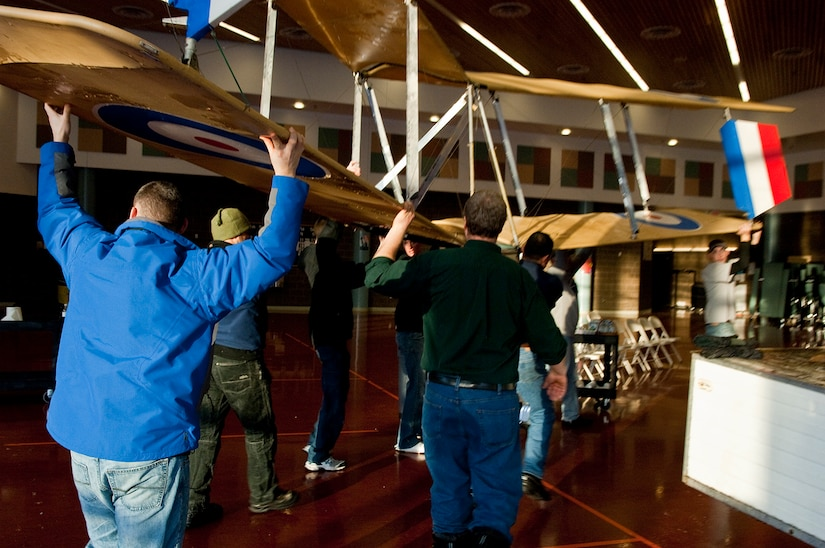 ANCHORAGE, Alaska -- Volunters from Joint Base Elmendorf-Richardson move an ultra-light model plane in Begich Middle School for the Build-a-Plane program Feb. 12. The Build-a-Plane program is designed to inspire children to become involved in aviation. (U.S. photo/Airman 1st Class Jack Sanders)
