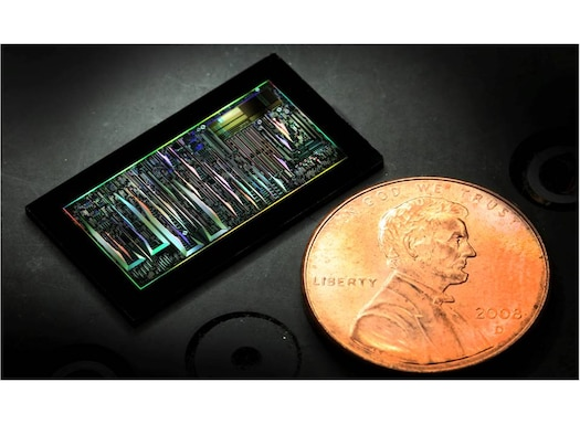A dark-field optical image of a silicon photonic chip is shown in