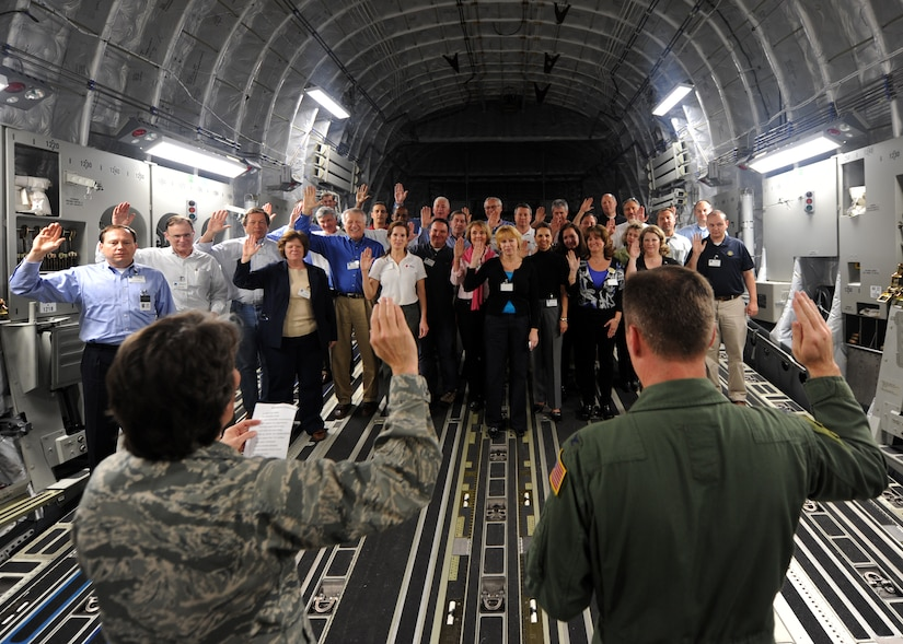 Col. Martha Meeker, left, and Col. John Wood, administer the oath of office to the new Honorary Commanders on board a C-17 Globemaster III Feb. 22 on Joint Base Charleston, S.C. More than 30 local area business people and community leaders became Honorary Commanders of various Air Force and Navy organizations at Joint Base Charleston. (U.S. Air Force photo/Senior Airman Timothy Taylor)