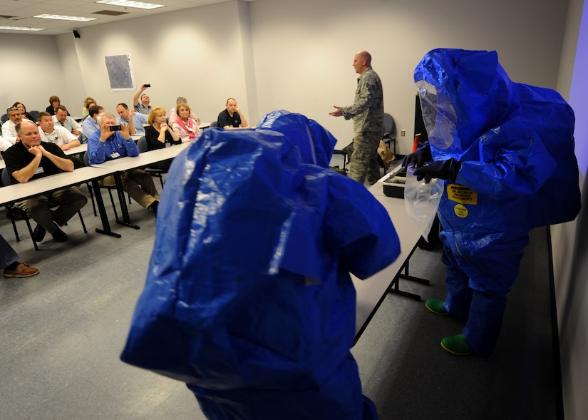 Staff Sgt. Brandon Barnes explains safety procedures in a contaminated environment during chemical, biological, radiological and nuclear training at the Logistics Readiness Squadron warehouse Feb 22 on Joint Base Charleston, S.C. During the CBRNE training, Honorary Commanders learned military procedures for detecting harmful airborne elements and protective safety measures. (U.S. Air Force photo/Senior Airman Timothy Taylor)