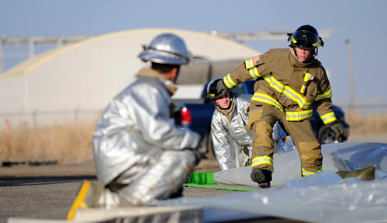 MOUNTAIN HOME AIR FORCE BASE, Idaho -- Members of the 366th Civil Engineering Squadron rush to lay down a tarp during a simulated chemical spill for the Unit Compliance Inspection Feb. 15. (U.S. Air Force photo be Airman 1st Class Renishia Richardson)