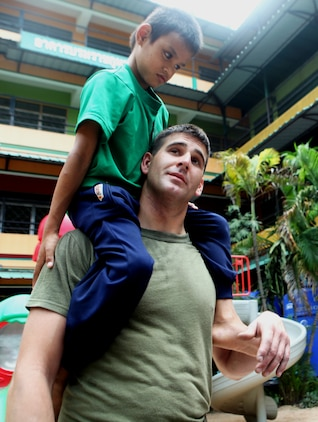Lance Cpl. Randolph Pitts, 22, of Vinalhaven, Maine, a heavy equipment mechanic with Combat Logistics Battalion 31, 31st Marine Expeditionary Unit, carries a blind Thai child on his shoulders during a community relations event, Feb. 24. Marines and Sailors assisted at the Father Ray Foundation School for the Blind during a port visit after the 31st MEU's successful conclusion of Cobra Gold 2011.  The 31st MEU is the nation's only continually forward deployed MEU, and remains a force-in-readiness in the Asia-Pacific region.