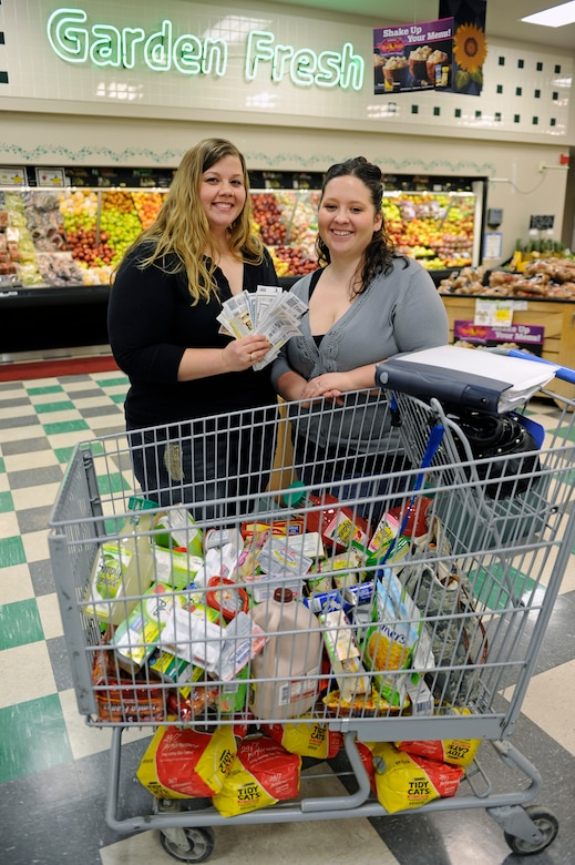 (Left) Mandy Morford and Whitney Burgett, Ellsworth Coupon Cutter page administrators, stand in front of a cart of groceries with a collection of coupons at the commissary at Ellsworth Air Force Base, S.D., Feb. 22, 2011.  They saved $88.75 on their groceries by using 77 coupons. (U.S. Air Force photo/Staff Sgt. Marc I. Lane)