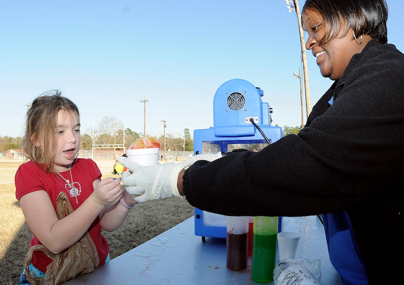 Nine-year old Jazmine Fraize spends her hard earned play money on a Sno Cone, one of the many items participants could purchase with their cash at the Learn and Earn Carnival at Menriv Soccer Field at Joint Base Charleston-Weapons Station, Feb. 23. The carnival was held in conjunction with Military Saves Week and is designed to teach children money management and savings through fun interactive games. (U.S. Navy photo/Mass Communication Specialist 1st Class Jennifer Hudson
