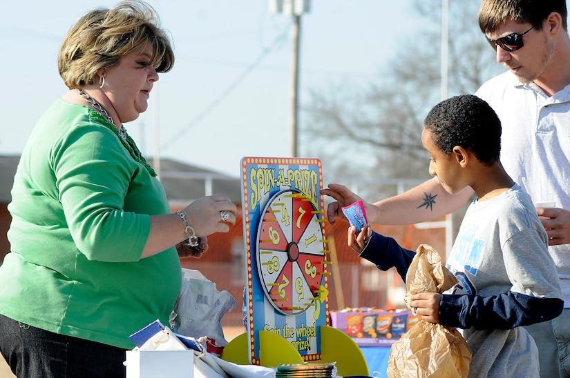 Nine-year-old Jermaine Mitchell receives his prize candy from Kim Brown, a financial specialist at the Fleet and Family Support Center, after spinning the 'Spin-a-Prize' wheel during the annual Learn and Earn Carnival at Menriv Soccer Field at Joint Base Charleston-Weapons Station, Feb. 23. The event was held in conjunction with Military Saves Week and is designed to teach children money management and savings through fun interactive games. (U.S. Navy photo/Mass Communication Specialist 1st Class Jennifer Hudson)