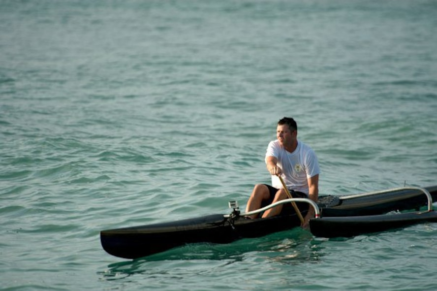 """Master Sgt. Jeff Allen, a strategic plans technician with the Pacific  Air Forces public affairs office at Joint Base Pearl Harbor Hickam, paddles a canoe through the waters off Hickam Beach Feb. 17. """"Paddling"""" is a popular local pastime in which paddlers brave the Pacific Ocean in outrigger canoes ranging in size from one to six passengers. (U.S. Air Force photo by Staff Sgt. Nathan Allen)"""