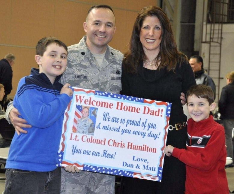 "FALMOUTH, Mass. - Lt. Col. Christopher Hamilton, 102nd Security Forces Squadron Commander, received a warm ""welcome home"" from his wife, Leslie, and their sons,  Daniel and Matthew, at a ceremony at Otis Air National Guard Base. The 102nd Intelligence Wing of the Massachusetts Air National Guard honored 42 airmen from the 102nd Security Forces Squadron (SFS) upon their return home from their deployment to Iraq. The wing held a welcome home ceremony to honor them and their families on Tuesday, Feb. 22, 2011. The Airmen have received mobilization orders last year and were deployed to Iraq for six-months in support of Operation New Dawn. Their primary responsibilities were to provide security and air base defense operations.  This was the largest number of 102nd SFS Airmen to deploy at the same time since Sept. 11, 2001.  In addition, it was the first time the squadron's command staff deployed as a group. (U.S. Air Force Photo by Maj. Lisa Ahaesy, Massachusetts National Guard)"