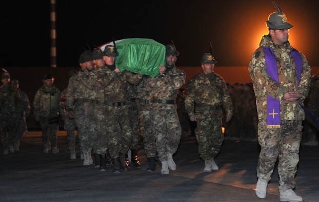 The flag-draped transfer case of Corporal Major (E-4) Matteo Miotto, an Italian soldier killed in western Farah Province, Afghanistan, Dec. 31, 2010, is carried to an Italian C-130 Hercules at Camp Arena, Herat Province, Jan. 1. Miotto's remains were returned to Rome. (U.S. Air Force photo/Tech. Sgt. Kevin Wallace)
