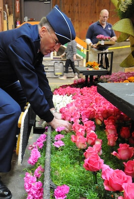 Brig. Gen. Scott Vander Hamm, Commander of the 509th Bomber Wing, Whiteman Air Force Base, Mo., places a rose on a parade float while visiting the Tournament of Roses' Decorating Places Dec. 31, 2010. A B-2 performed the flyover over this year's 122nd annual parade. (Photo by Joe Juarez)