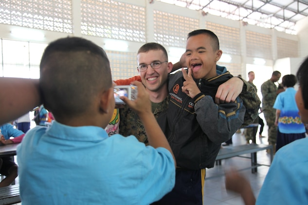 Sgt. Ian Trenkel a radio operator with Marine Air Support Squadron 2, Marine Air Control Group 18, 1st Marine Aircraft Wing, III Marine Expeditionary Force, poses with children from the Panyoonnookun School for Disabled in Korat, Kingdom of Thailand, Feb. 4, 2011. The Marines and sailors are in Thailand for Exercise Cobra Gold 2011, an annual Thai/U.S. co-sponsored joint and multinational exercise.