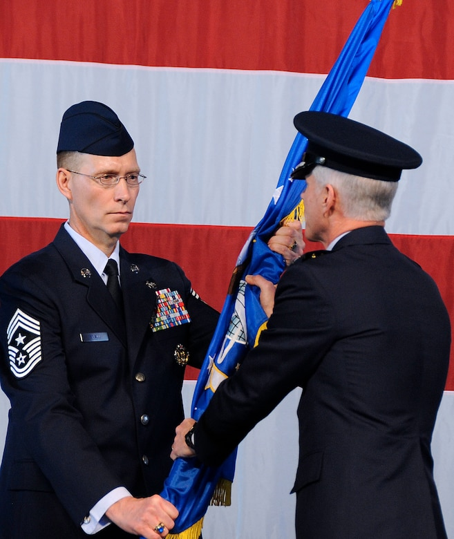 Gen. William L. Shelton receives the Air Force Space Command guidon from Chief Master Sgt. Richard T. Small, becoming the 15th commander of AFSPC during the change of command ceremony Jan. 5, 2011, at Peterson Air Force Base, Colo. Chief Small is the command chief master sergeant of AFSPC. (U.S. Air Force photo/Duncan Wood)