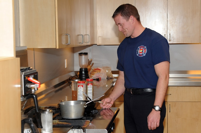 BUCKLEY AIR FORCE BASE, Colo.--Jason Debord, a fire fighter at Buckley Air Force Base cooks himself dinner, Jan. 4, 2011. Each fire fighter has to cook their own dinner and clean up after themselves, with the occasional fire station dinner where they all eat together. (U.S. Air Force photo by Airman Manisha Vasquez)