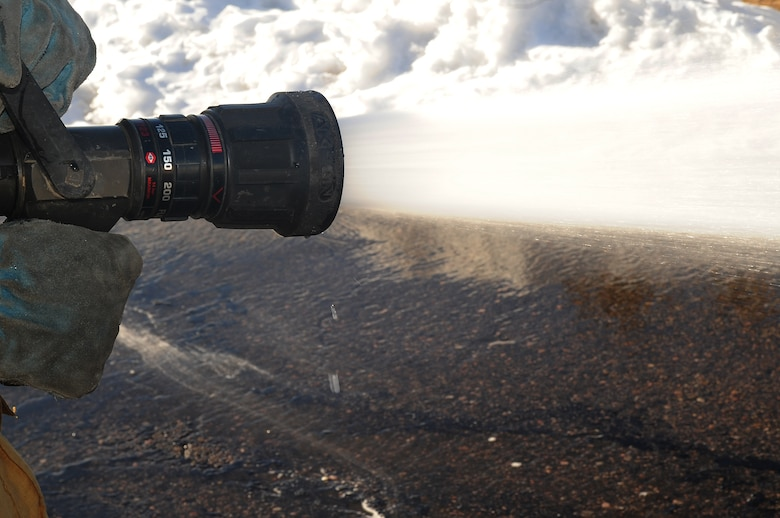 BUCKLEY AIR FORCE BASE, Colo.-- A fire hose from the main engine sprays about one-hundred and fifty pounds of water per square inch, Jan. 4, 2011. The buckley fire department get called for emergency's about five times a day on average. (U.S. Air Force photo by Airman Manisha Vasquez)