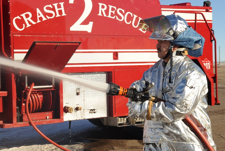 BUCKLEY AIR FORCE BASE, Colo.-- Carlos Hidalgo from the Buckley Fire Department sprays water from one of the six trucks, Jan. 4, 2011. Each fireman works forty-eight hours on shift and seventy-two off.  (U.S. Air Force photo by Airman Manisha Vasquez)