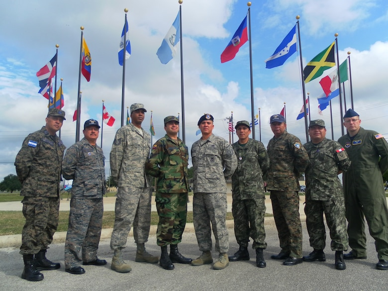 INCOA class 10-C stands for a group photo outside the school. From left to right, the picture includes:  S/O Mayor (E-8) Denis Paz of Honduras; SGTO. Mayor (E-8) Walter Avila of Guatemala; Tecg Sgt. Leonardo Cepero of the United States Air Force; Suboficial (E-7) Edgar Yandun of Ecuador (Guest Instructor); Master Sgt. Benjamin Miranda of the United States Air Force (Instructor); TC3. FAP. (E-7) Miguel Ochoa of Peru; SGTO. TEC. (E-7) Byron Flores of Guatemala; TC1. FAP. (E-8) Walter Vivas of Peru; and Tech Sgt. George Nikolakakos of the United States Air Force.