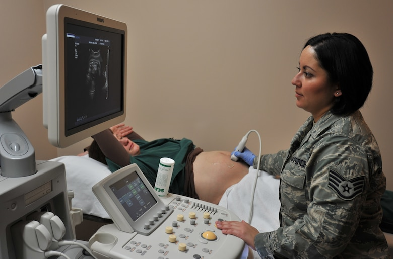 Photo of  a woman in military uniform performing an ultra sound on another woman.
