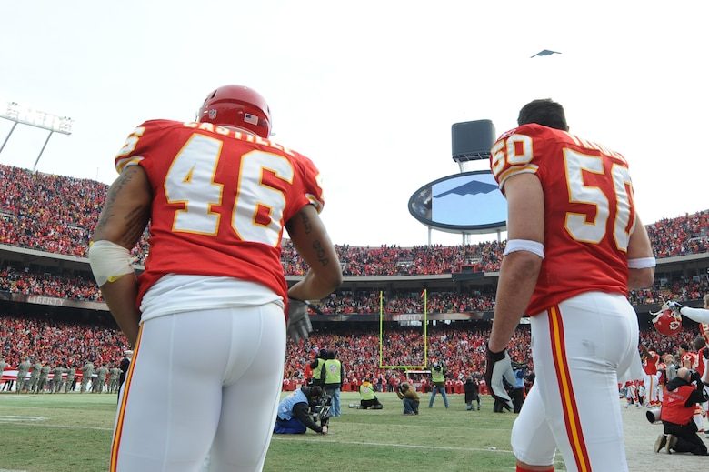 KANSAS CITY, Mo. - Tim Castille, a running back, and Mike Vrable, a linebacker for the Kansas City Chiefs, watch as a B-2 stealth bomber from the 509th Bomb Wing flies overhead during the opening ceremonies of the Kansas City Chief's Wild Card play-off game Jan 9. (U.S. Air Force photo by Senior Airman Carlin Leslie)