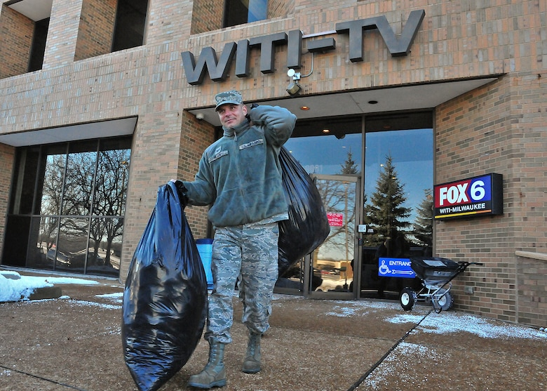 Milwaukee Air Guardsman Tech. Sgt. Chance Biller carries bags of donated winter coats from the Fox 6 Milwaukee studio to a Salvation Army van Friday, 10 Dec. 2010.
