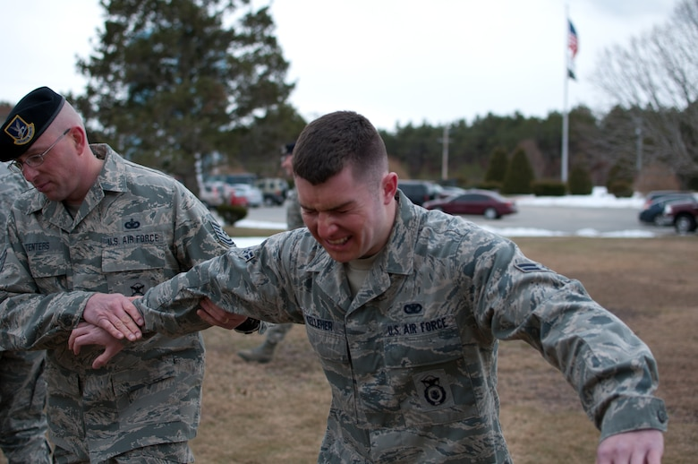 Airman 1st Kelleher of the 102nd Security Forces Suadron is escorted to an aid station by Technical Sgt. Tenters after being sprayed with Cap-Stun pepper-spray and confronting an aggressor as part of a security forces training event held on Otis Air National Guard Base, Mass. on January 9, 2011. Security Forces airmen were sprayed with the pepper-spray so they are familiar with it's affects and can still perform their duties if they come in contact with it.